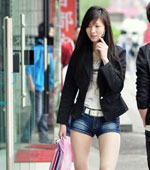Chinese girl in short pants walking around town