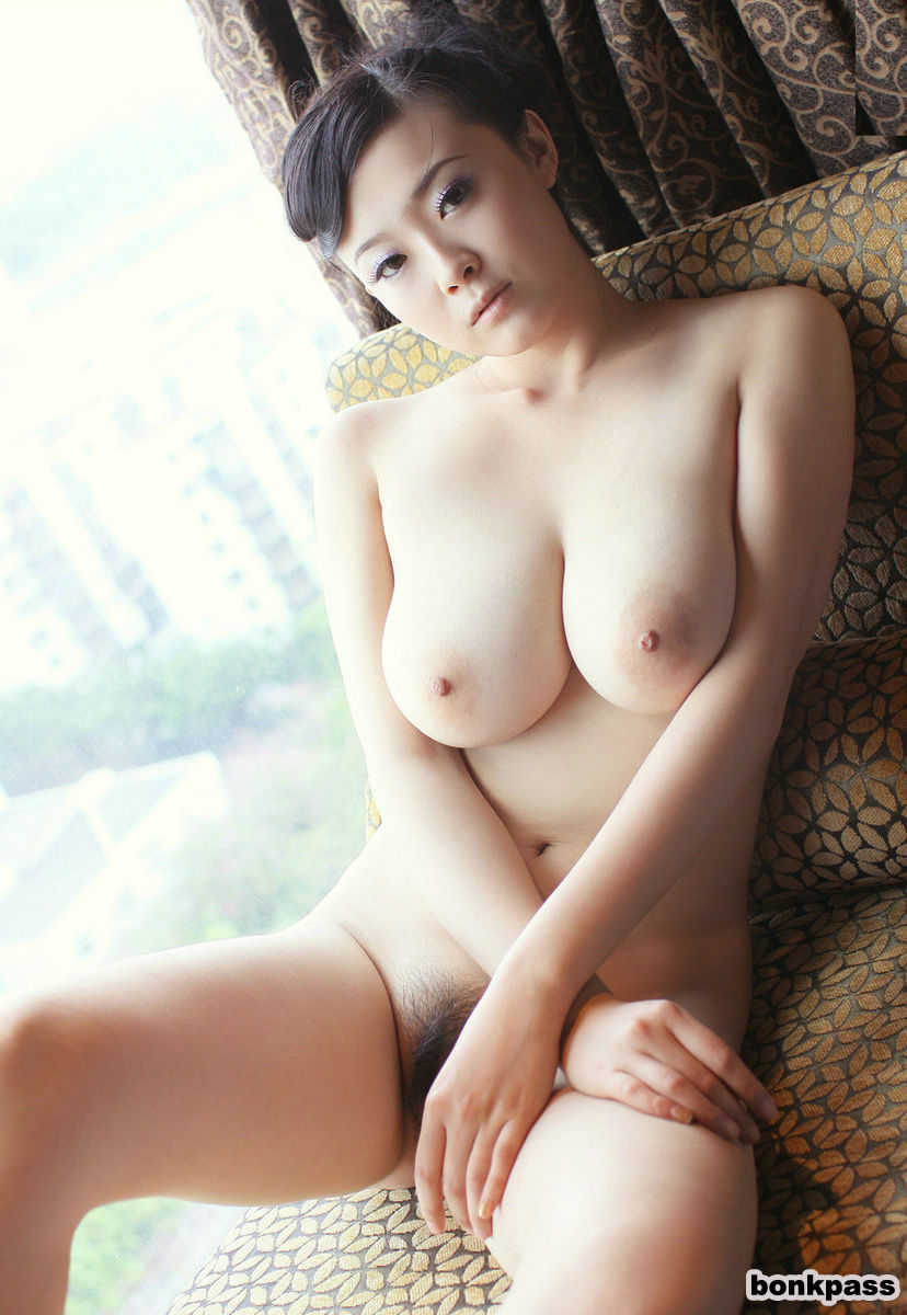 Busty Chinese babe posing nude on sofa